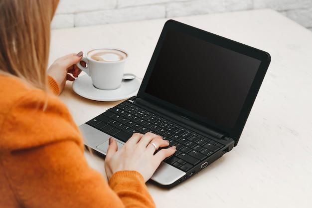 Ragazza bionda in un caffè con un computer portatile e caffè. free lance della ragazza che lavorano ad un computer portatile