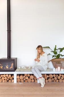 Ragazza bionda lavora a maglia seduta su un cuscino accanto al camino in un accogliente interno scandinavo