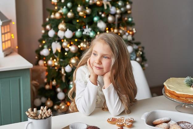 Ragazza bionda nella cucina del nuovo anno con cupcakes e dolci