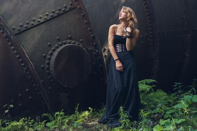 Ragazza bionda nella vecchia fabbrica abbandonata del vestito nero