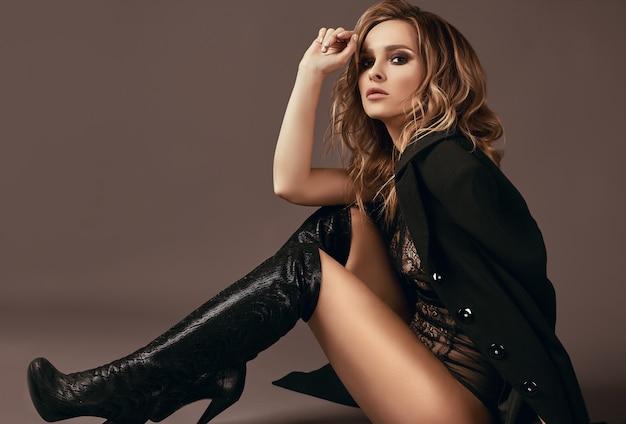 Ragazza bionda seducente sexy in biancheria intima, cappotto nero e stivali