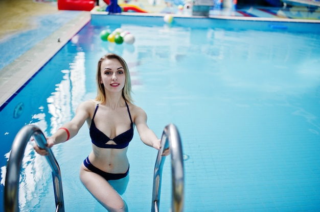 Ragazza bionda sexy in costume da bagno blu che ha resto nella piscina del parco dell'acqua.