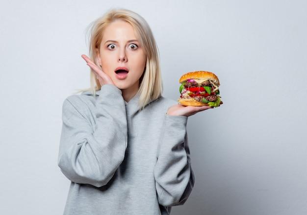 Ragazza bionda sorpresa con hamburger