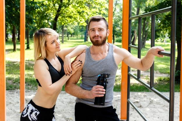 Ragazza bionda sportiva e uomo barbuto che riposano dopo l'allenamento di allenamento in un parco all'aperto. uomo che tiene una bottiglia nera con acqua.