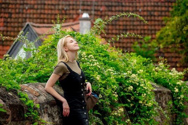 Ragazza bionda stare vicino a vecchie case di piastrelle di città in europa