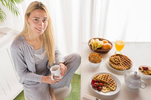 Ragazza bionda sul tavolo della colazione