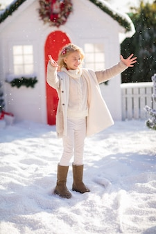Ragazza bionda sveglia che gioca con la neve vicino alla casetta e gli alberi innevati