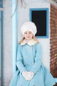 Ragazza bionda sveglia in un cappotto blu e cappello di pelliccia bianco in inverno. tempo nevoso. la ragazza sotto il portico della casa. casa invernale. modello in posa sulla strada. il concetto di vacanze invernali.