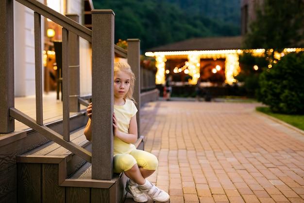 Ragazza bionda triste 9 anni in vestiti gialli che si siedono sulle orme di legno del ristorante