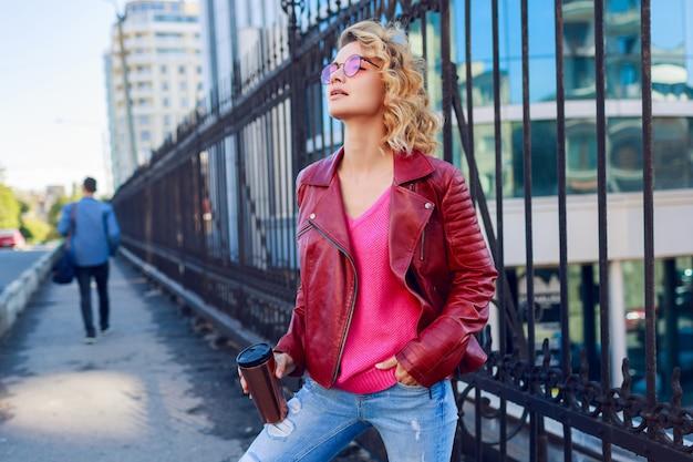 Ragazza bionda vaga che cammina per le strade, bevendo caffè o cappuccino. elegante abito autunnale, giacca di pelle e maglione lavorato a maglia. occhiali da sole rosa.