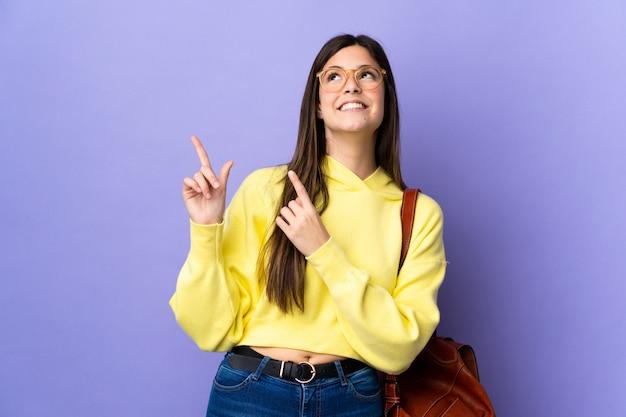 Ragazza brasiliana dello studente dell'adolescente sopra fondo porpora isolato che indica con il dito indice una grande idea