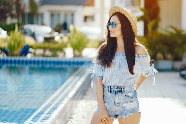 Ragazza bruna abbronzatura e relax in piscina