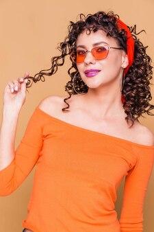Ragazza bruna alla moda in un maglione arancione brillante, occhiali e una bandana in posa sull'arancio