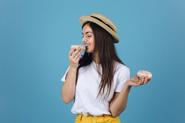 Ragazza bruna assaggia una ciambella in posa in un cappello