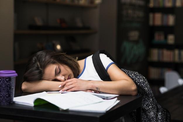 Ragazza bruna che dorme appoggiata sul tavolo