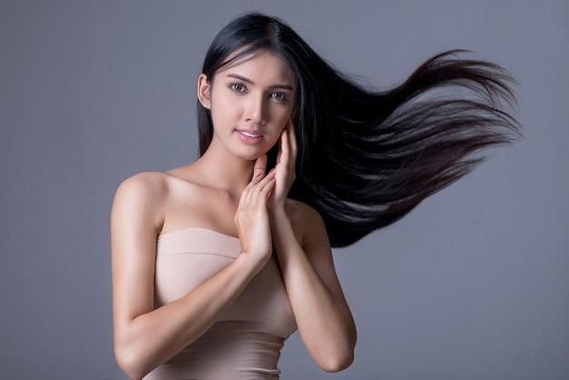 Ragazza bruna con capelli ondulati lunghi e lucenti