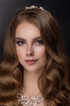 Ragazza bruna con capelli ricci lunghi e lucenti.