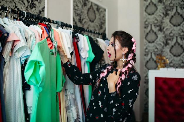 Ragazza bruna con i capelli colorati sorpreso guardando il prezzo del vestito verde.