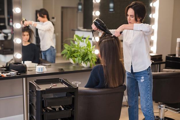 Ragazza bruna, farsi asciugare i capelli
