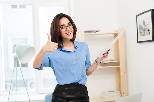 Ragazza bruna in camicia blu e gonna nera è in piedi in ufficio. tiene la carta in mano. sembra molto felice con un ampio sorriso.
