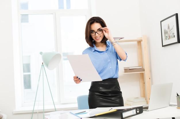 Ragazza bruna in camicia blu e gonna nera è in piedi vicino al tavolo in ufficio. tiene gli occhiali sul viso e la carta in mano. sta guardando alla telecamera.