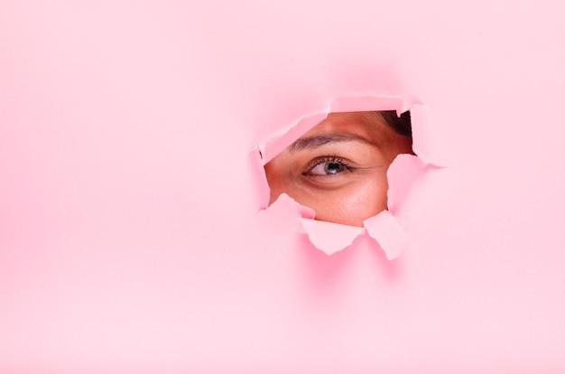 Ragazza bruna in posa attraverso un buco di carta