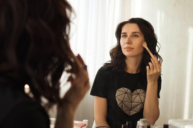 Ragazza bruna mette il trucco davanti allo specchio, riflesso nello specchio