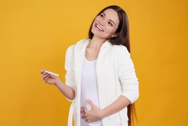 Ragazza bruna pone con test di gravidanza.