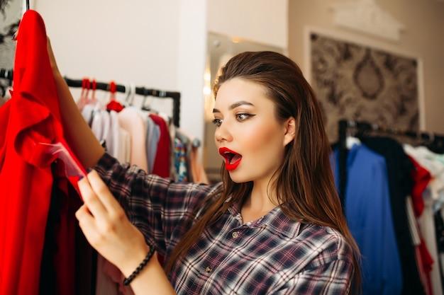 Ragazza bruna sorpresa guardando il prezzo del vestito rosso con la bocca aperta.