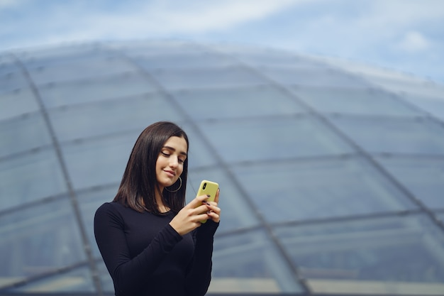 Ragazza bruna usando il suo cellulare mentre sta esplorando una nuova città