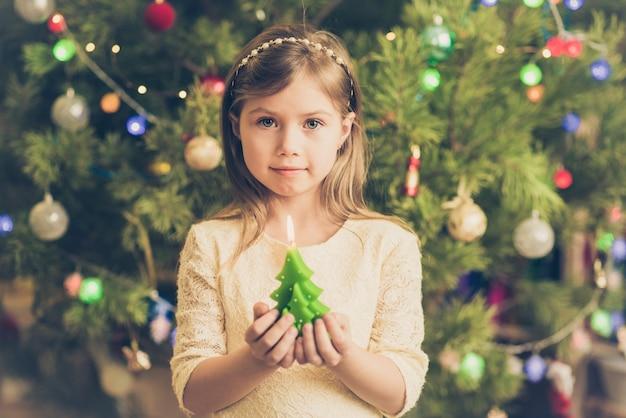 Ragazza carina a natale con una candela in mano