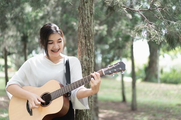 Ragazza carina a suonare la chitarra in giardino