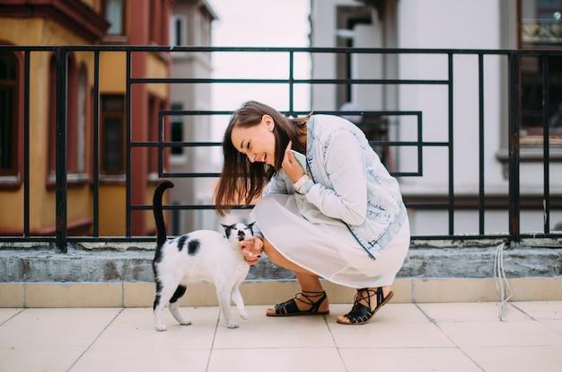 Ragazza carina accarezzando un gatto randagio sulla strada e sorridente