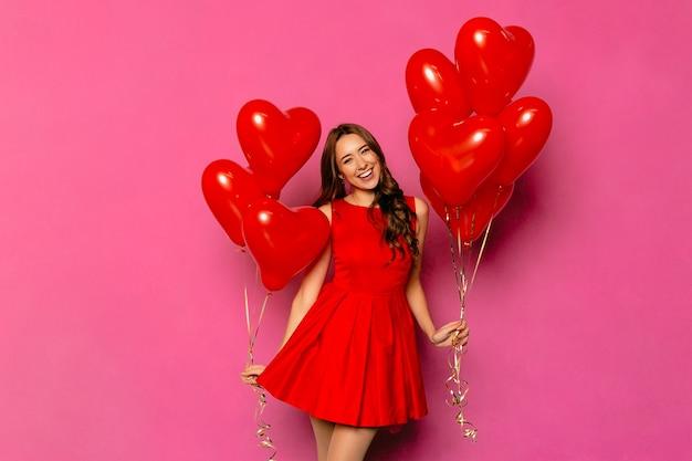 Ragazza carina allegra con capelli ricci lunghi in vestito rosso che tiene gli aerostati