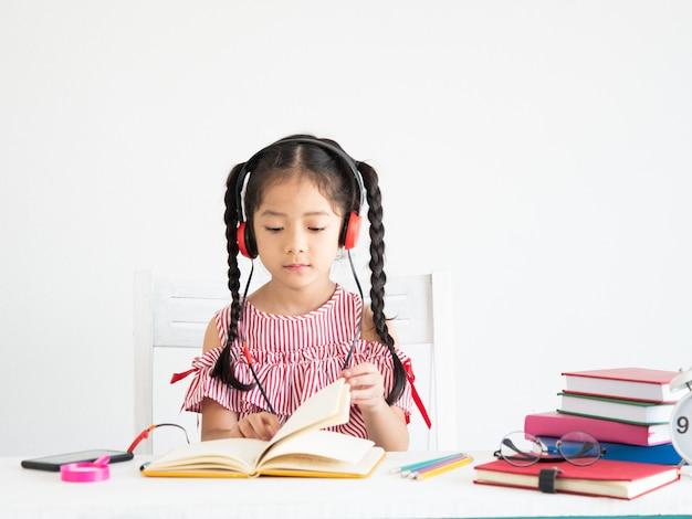 Ragazza carina asiatica con il libro sulla scrivania