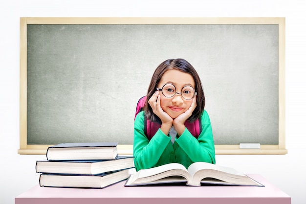 Ragazza carina asiatica con occhiali e zaino con libri sulla scrivania