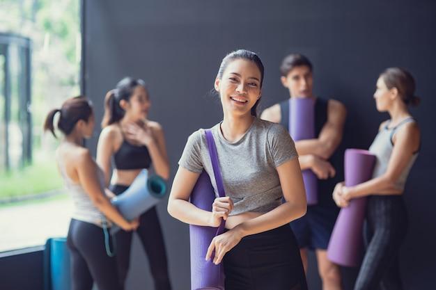 Ragazza carina asiatica seduta nella parte anteriore gruppo di razza mista di persone caucasiche e asiatiche, uomini e donne parlano e ridono al muro nero in attesa di godersi insieme la lezione di yoga