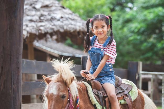 Ragazza carina bambino asiatico cavalcando un pony in fattoria con divertimento
