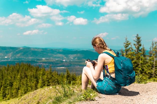 Ragazza carina bionda con uno zaino e occhiali si siede su una montagna e gode le splendide colline delle montagne in una giornata di sole.