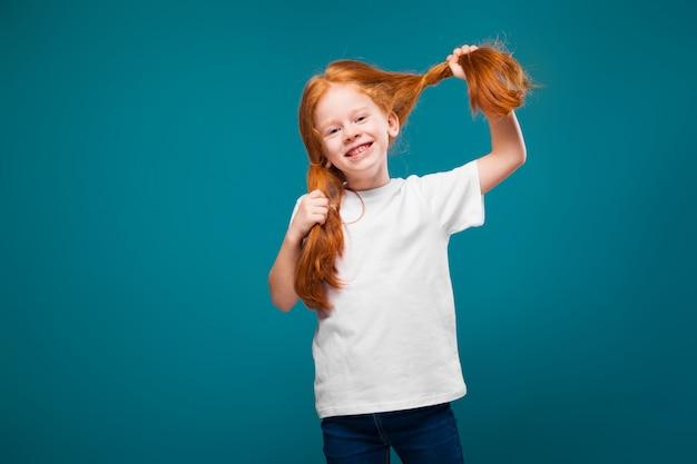 Ragazza carina, carina, in maglietta con lunghi capelli rossi
