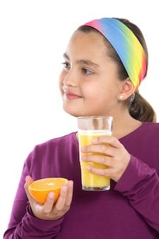 Ragazza carina che beve succo di arance su uno sfondo bianco
