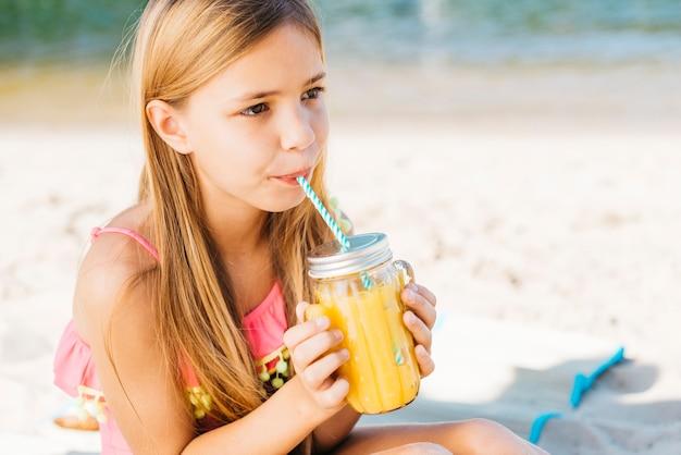 Ragazza carina che beve succo in riva al mare