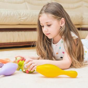Ragazza carina che gioca con i giocattoli a casa