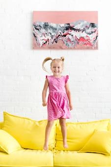 Ragazza carina che salta sul divano giallo