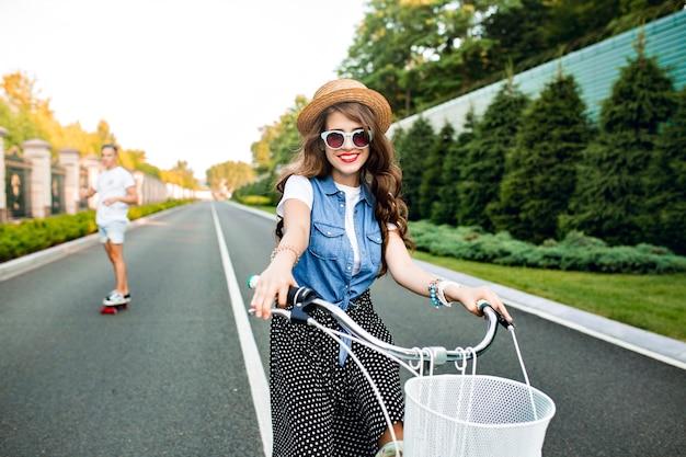 Ragazza carina con capelli ricci lunghi in occhiali da sole alla guida di una bici alla telecamera sulla strada. indossa gonna lunga, farsetto, cappello. bel ragazzo sta cavalcando su skateboard sullo sfondo.