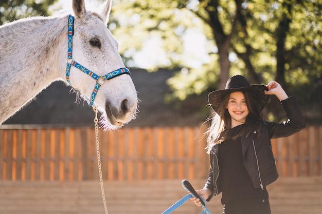 Ragazza carina con cavallo bianco
