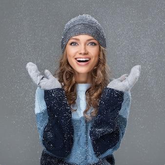 Ragazza carina con fiocchi di neve che si divertono