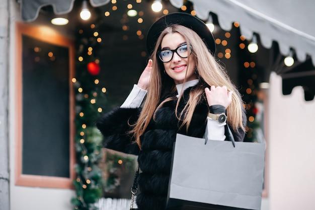 Ragazza carina con gli occhiali cammina per le strade di natale della città facendo shopping di capodanno