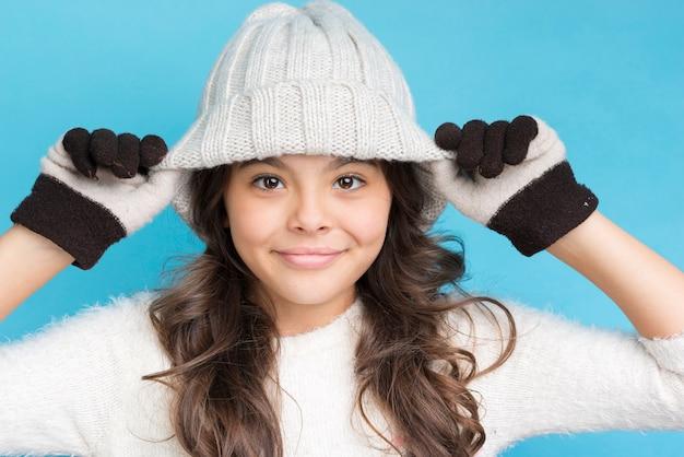 Ragazza carina con guanti e cappello sulla testa