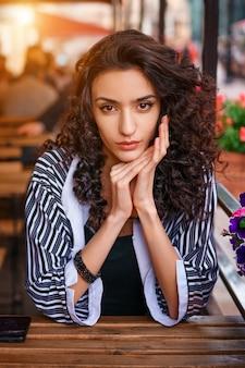 Ragazza carina con i capelli ondulati, ritratto di una ragazza in un caffè.